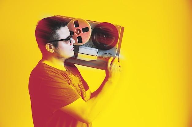 Человек, держащий пластинку. парень с катушечным магнитофоном. партийные идеи. дискотека в стиле ретро. винтажная музыка.