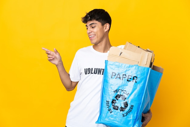 Man holding a recycling bag full of paper to recycle over isolated yellow background pointing finger to the side and presenting a product