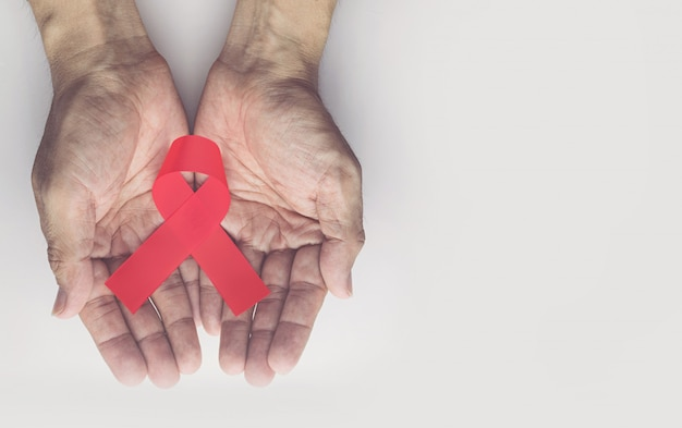 Man holding red aids ribbon, hiv/aids and aging awareness month concept
