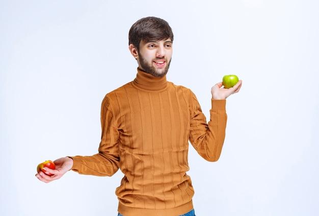Мужчина держит красные и зеленые яблоки в обеих руках.