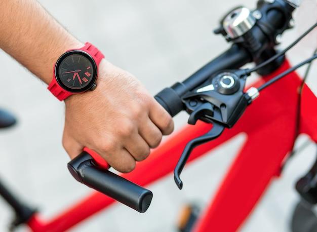 Мужчина держит красный велосипед крупным планом