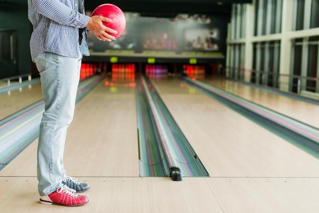 Uomo che tiene una palla da bowling rossa