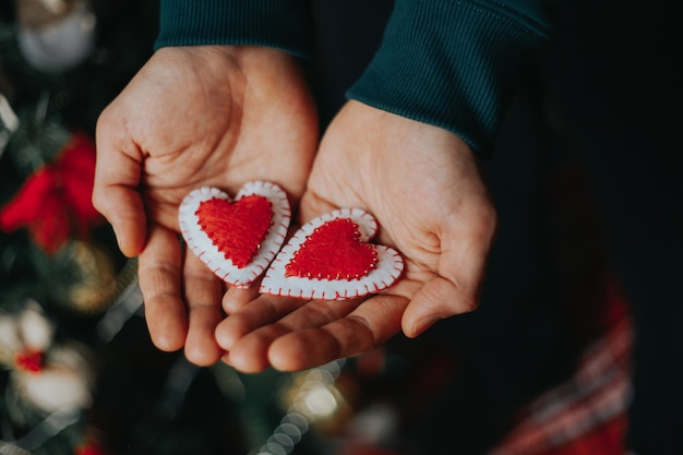 Man holding red felt hearts in his hands