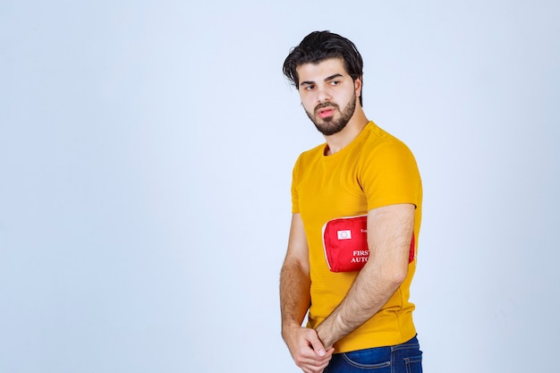 Man holding a red first aid kit under his arm.