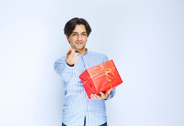 Man holding a red gift box and asking for money. high quality photo