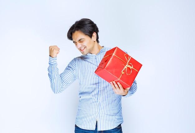 Uomo che tiene in mano una confezione regalo rossa e si sente di successo. foto di alta qualità