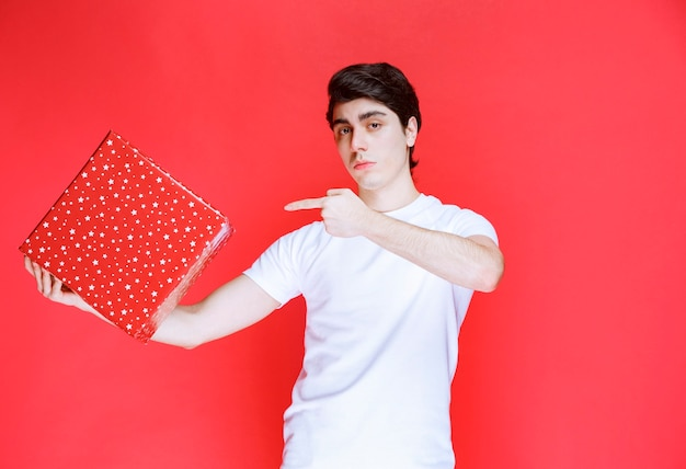 Man holding a red gift box and pointing at it