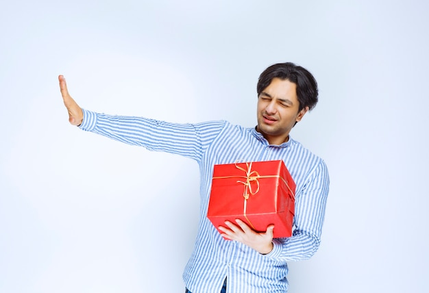 Uomo che tiene una confezione regalo rossa e ferma qualcuno. foto di alta qualità