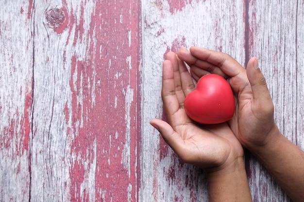 木製のテーブルに手で赤いハートを抱きかかえた