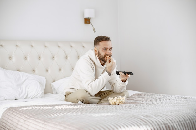 Man holding remote control with popcorn bowl