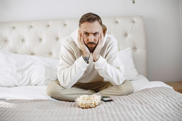 Uomo con telecomando con ciotola di popcorn