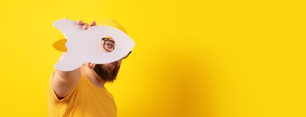 Man holding rocket over yellow background, guy with successful startup, panoramic layout