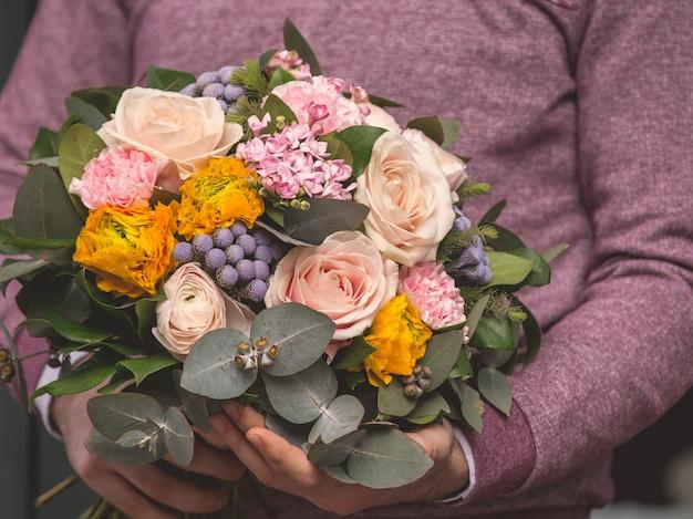 Uomo che tiene un bouquet romantico di fiori di selezione mista e pronto ad offrire