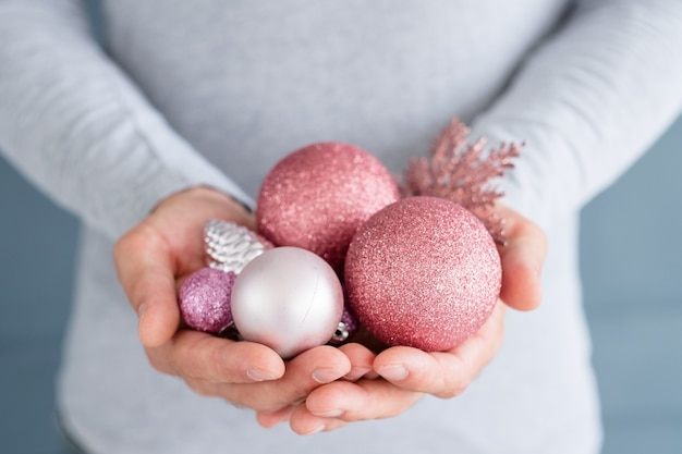 Man holding rose gold glittery baubles in hands.