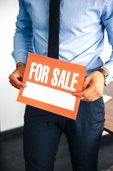 Man holding for sale sign
