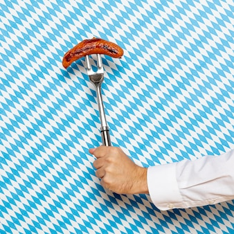 Man holding sausage with patterned background