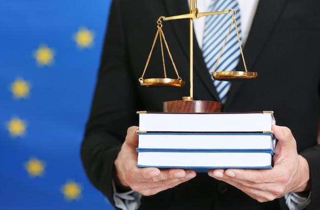 Мужчина держит весы и юридические книги на фоне флага европейского союза
