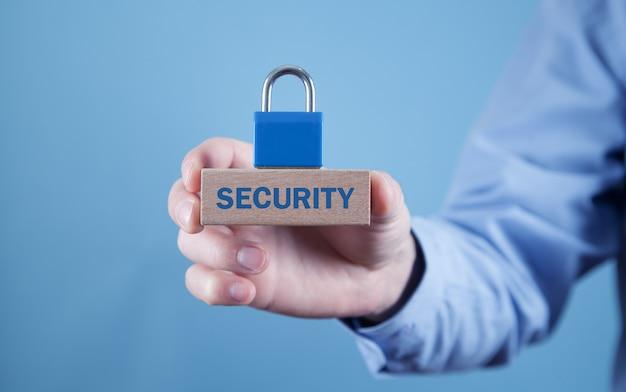 南京錠で木製のブロックにセキュリティワードを保持している男。