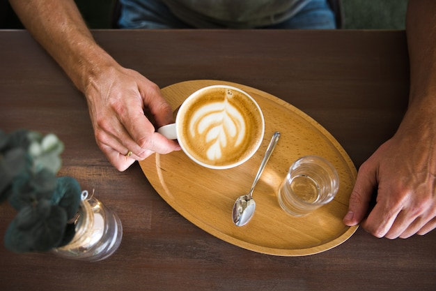 A man holding serving cup of coffee cappuccino and a glass of water on a wooden tray. view from above