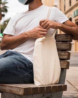 Мужчина держит сумку и сидит на скамейке