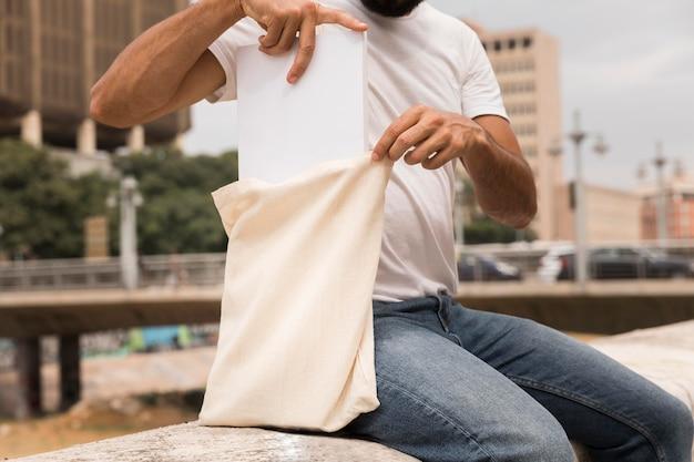 Мужчина держит сумку и сидит