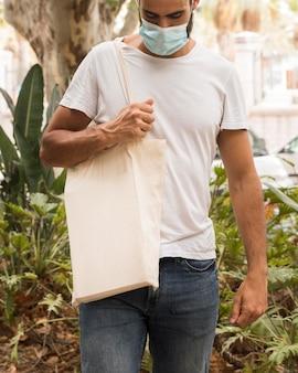 Человек, держащий хозяйственную сумку и ходьбу вид спереди