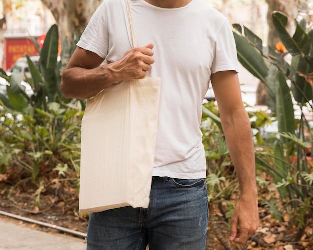 Мужчина держит сумку и гуляет