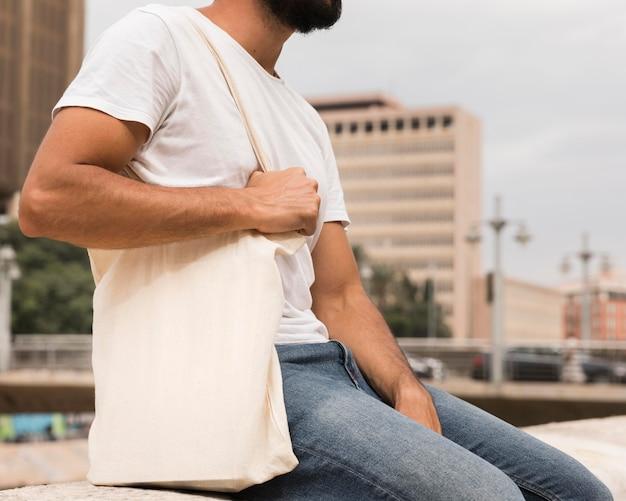 Человек, держащий хозяйственную сумку в городе