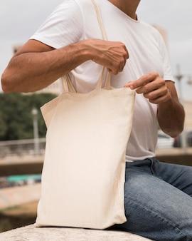 Man holding shopping bag and wearing white shirt