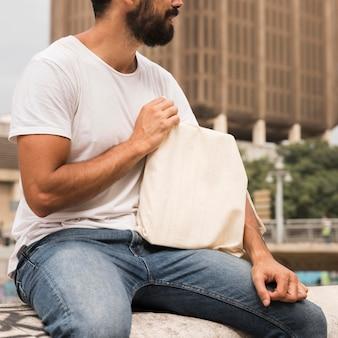 Человек, держащий хозяйственную сумку