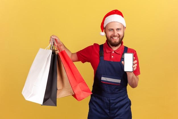 Человек, держащий сумки и смартфон, смотрит в камеру с зубастой улыбкой в интернет-магазине