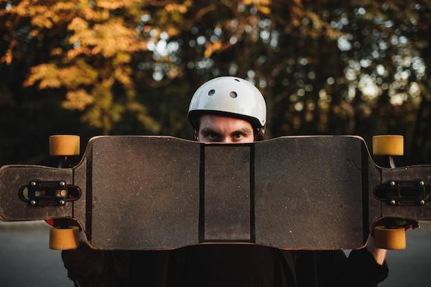 日没時にスケート、ロングボードを保持している男。高品質の写真