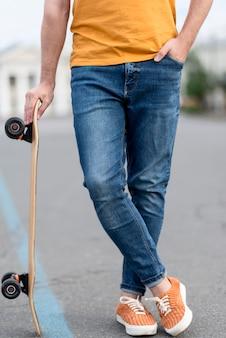 Uomo che tiene una vista frontale di skateboard