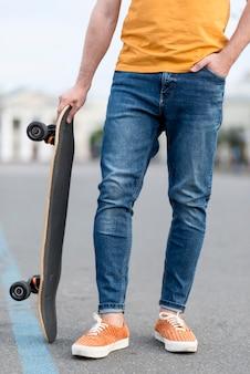 Uomo che tiene uno skateboard e una mano in tasca