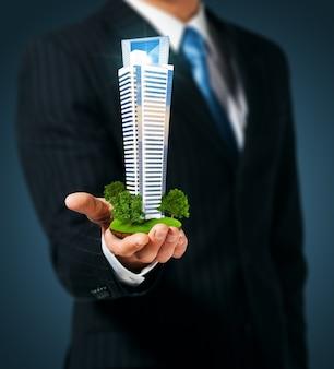 Man holding a skyscraper  in hand