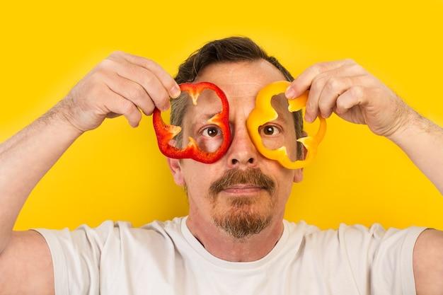 眼鏡のように彼の目に赤と黄色のピーマンのスライスを保持している男
