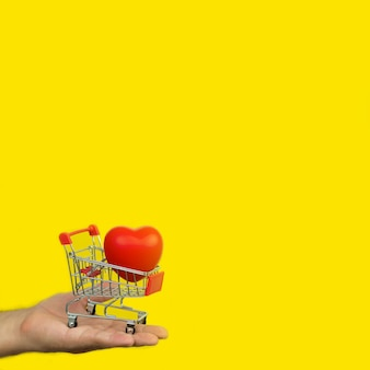 Man holding small cart with red heart on yellow background