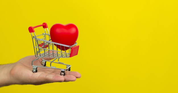 Man holding small cart with red heart on yellow background.