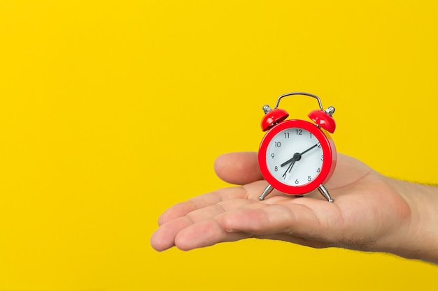 Man holding small red alarm clock on yellow background. time management concept