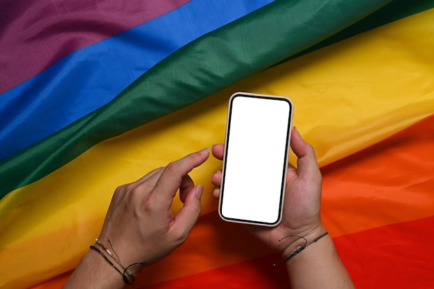 Man holding smart phone with blank screen over colorful rainbow flag. lgbt.