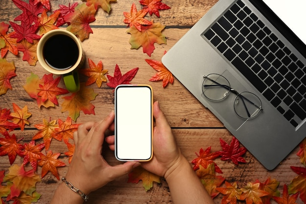 Man holding smart phone on wooden table with autumn maple leaves.