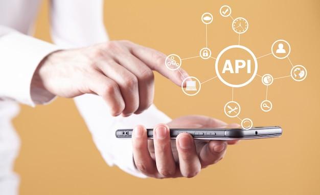 スマートフォンを持っている男。 api。アプリケーションプログラミングインターフェイス。ソフトウェア開発。テクノロジー