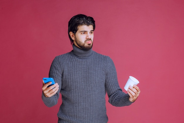 Uomo che tiene uno smartphone e una tazza di caffè e sembra confuso.
