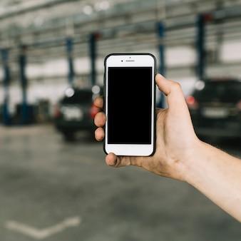 Man holding smartphoneat garage