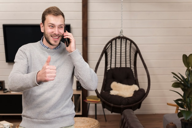 Man holding smartphone and giving thumbs up at home
