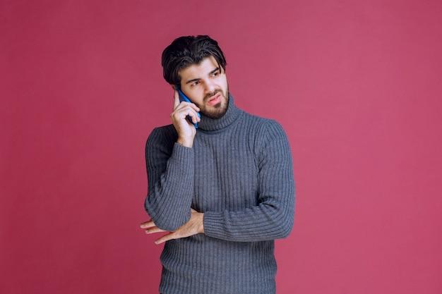 Uomo che tiene uno smartphone all'orecchio e parla.