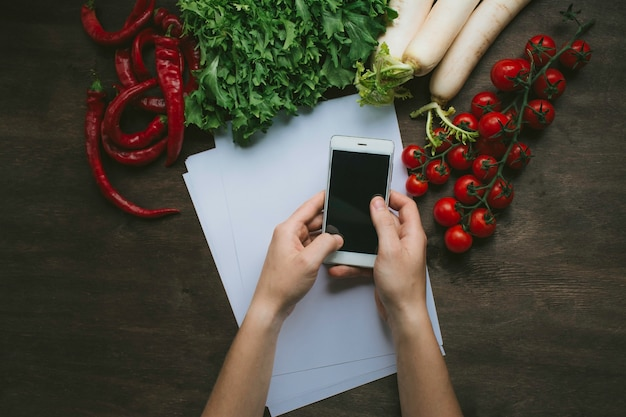 A man holding a smartphone in his hands on the kitchen table on a background with fresh vegetables. flat lay