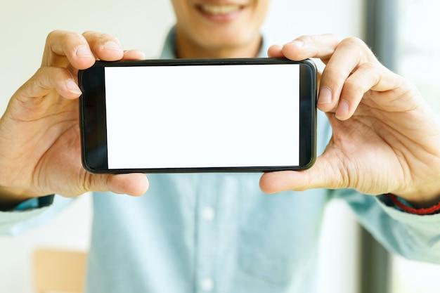 スマートフォンを手に持っている男。スマートフォンを示すビジネスマン。