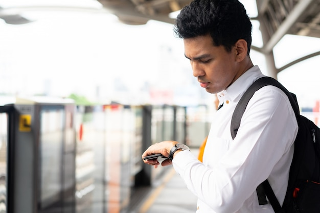 Man holding smartphone and looking watch on hand for checking the time schedule of train at station