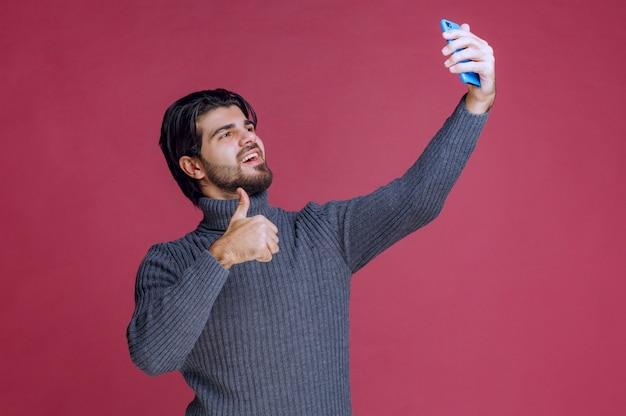Uomo che tiene uno smartphone, effettua una videochiamata o prende selfie.